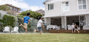 Two young brothers playing in a backyard, racing towards parents waiting at the house.
